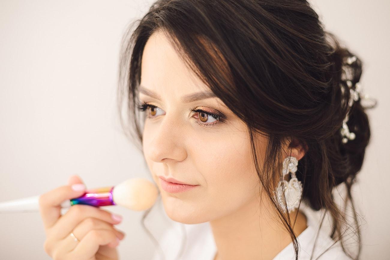 Panna Młoda aplikująca pędzelem puder transparentny by utrwalić makijaż.