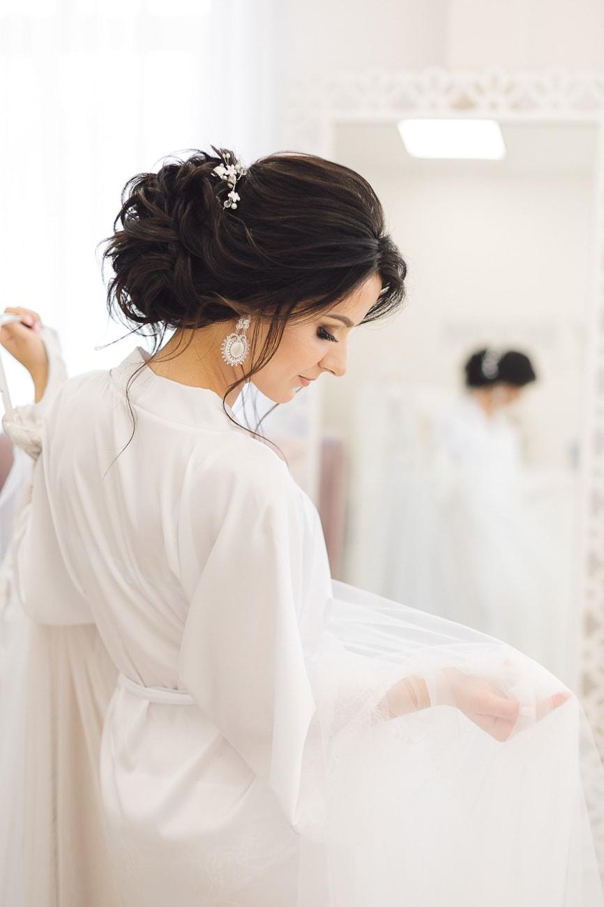 Panna Młoda w szlafroku trzymająca sukienkę ślubną