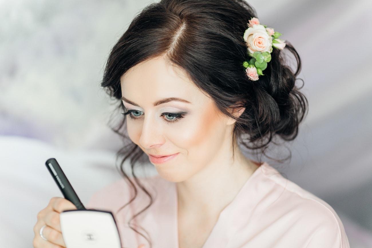 Kobieta nakładająca makijaż podczas przygotowań do ślubu
