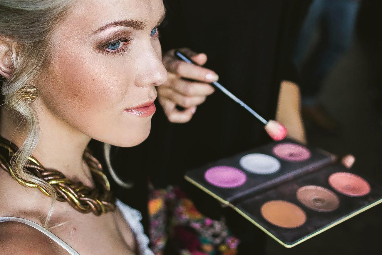 Wizażystka nakładająca makijaż u Panny Młodej w postaci różu i bronzera